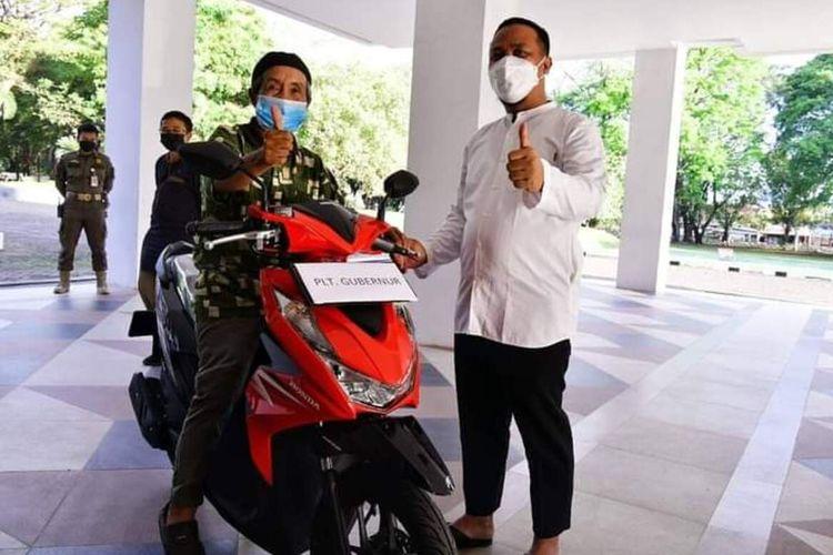 Safaruddin (64) tengah menerima pemerian hadiah sepeda motor oleh Plt Gubernur Sulawesi Selatan. Jumat, (30/7/2021)