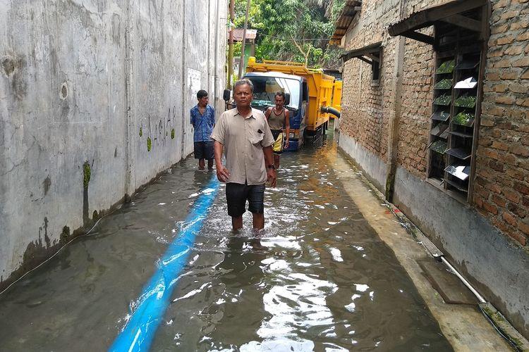 Warga di gang Subur Lama, Lingkungan 16-17, Kelurahan Kampung Baru, Kecamatan Medan Maimun melintas di genangan banjir yang tak surut sejak 1,5 bulan yang lalu.