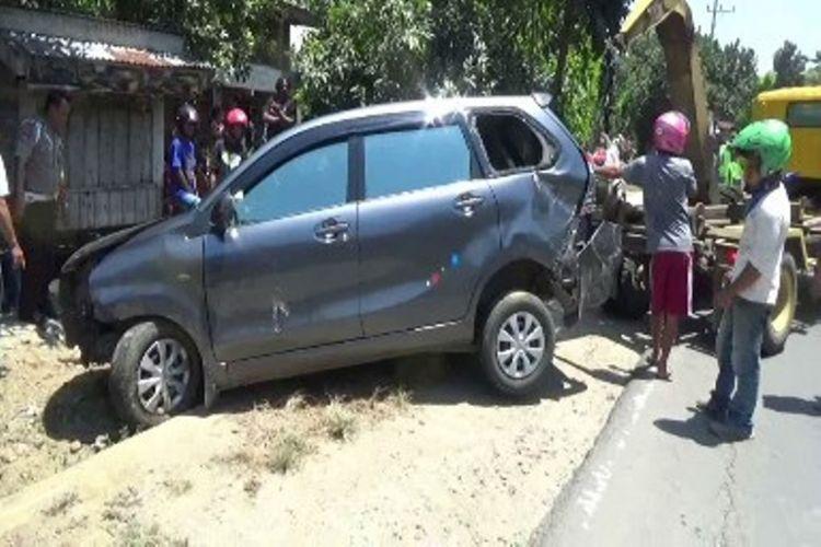 Mobil Toyota Avanza menabrak pagar tembok hingga roboh dan terguling ke dalam parit.