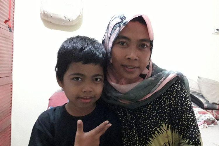 Alvin (8) dan Lasmawati (38) ibunya yang kini telah pindah kembali ke Jakarta setelah berjuang pulang pergi sekolah dari Parung selama 7 bulam lamanya saat dijumpai di Rusun Bendungan Hilir 2, Jakarta Pusat pada Selasa (23/4/2018).