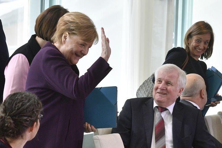 Kanselir Jerman Angela Merkel (kiri) tertawa seraya mengangkat tangannya pada 2 Maret 2020. Momen itu terjadi setelah Menteri Dalam Negeri Horst Seehofer menolak jabat tangan dengannya di tengah penyebaran virus corona.