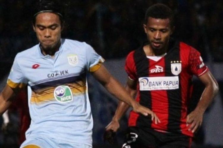 Gelandang muda Persipura, Friska Womsiwor (kanan), mencoba melewati pemain Persela Lamongan pada laga pekan ke-11 Liga 1 musim 2017 di Stadion Surajaya, Lamongan pada 14 Juni 2017.