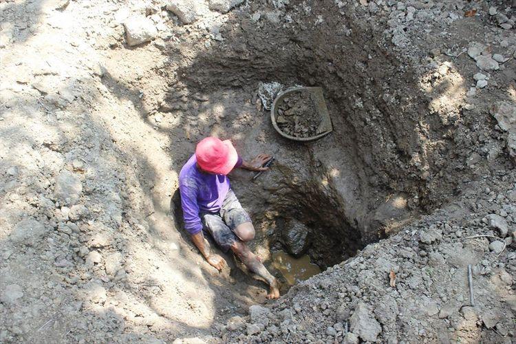 Seorang warga di Kp. CIsalak Hilir, Desa Cisalak, Kec. Cibeber, Kab. Cianjur, Jawa Barat sedang menggali tanah untuk mencari sumber air baru karena bencana kekeringan