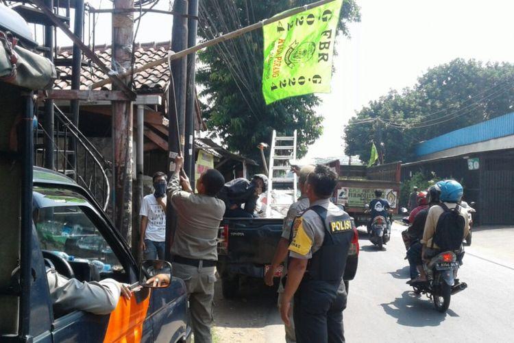 Petugas Satpol PP dan polisi mencopot bendera ormas di Ulujami, Jakarta Selatan, Kamis (27/7/2017).