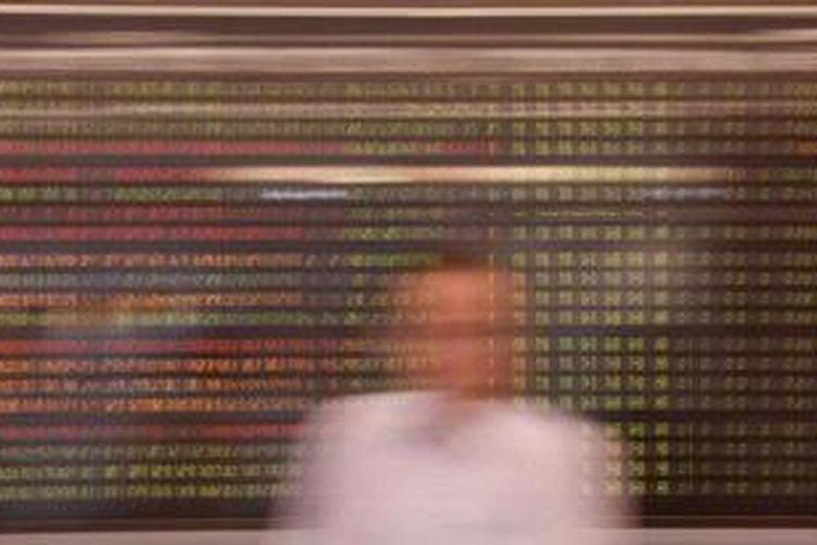 Pengunjung melintas di dekat monitor yang menunjukkan perkembangan indeks harga saham gabungan (IHSG)