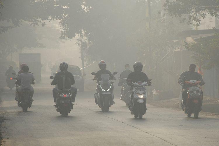 Sejumlah pengendara melintas menembus asap akibat kebakaran di Tempat Pembuangan Akhir (TPA) Antang Makassar, Sulawesi Selatan, Rabu (18/9/2019). Kebakaran sampah di TPA Antang yang terjadi sejak Minggu (15/9/2019)  tersebut mengakibatkan sebagian daerah di Makassar dan Kabupaten Gowa diselimuti asap pada pagi hari yang dapat mengganggu kesehatan pernapasan.