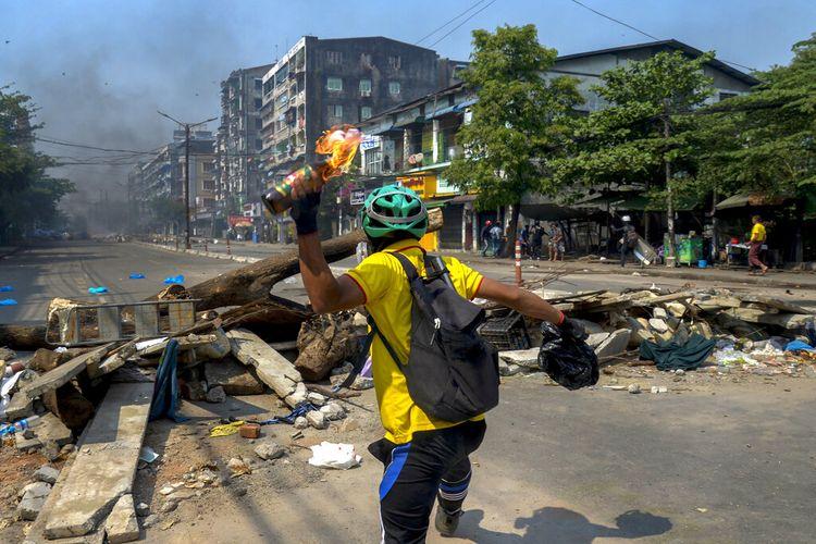 Seorang pengunjuk rasa anti-kudeta melemparkan bom molotov ke arah polisi saat mereka bergerak menuju area protes di Yangon, Myanmar pada Rabu (17/3/2021).