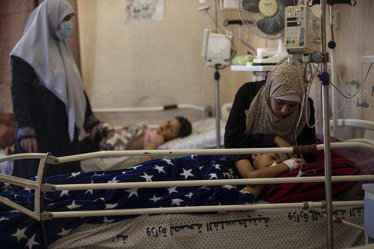 Ibu dari Yazan Al-zaharna, 9, menghiburnya saat dia beristirahat di rumah sakit Shifa di Kota Gaza, Kamis, (13/5/2021), di mana dia menerima perawatan untuk luka yang disebabkan oleh serangan Israel 10 Mei di dekat rumahnya di kota Jabaliya.