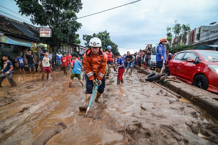 Petugas pemadam kebakaran Kota Bandung membersihkan lumpur akibat banjir bandang di Jalan AH Nasution, Bandung, Jawa Barat, Selasa (20/3/2018). Banjir bandang yang disertai lumpur tersebut disebabkan oleh luapan Sungai Cipamokolan akibat intensitas hujan yang tinggi di beberapa wilayah Kota Bandung.