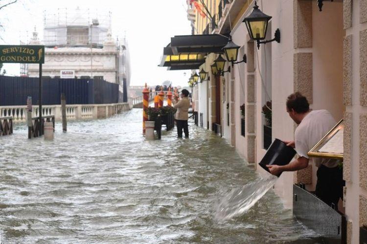 Seorang pria tampak membuang air banjir yang masuk dengan menggunakan ember di Venesia, Italia, Senin (29/10/2018). (AFP/Miguel Medina)
