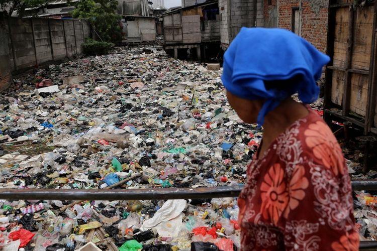 Warga melintas di Kali Gendong, Waduk Pluit, Penjaringan, Jakarta Utara, Selasa (14/3/2017). Kurangnya kesadaran masyarakat membuang sampah sembarangan mengakibatkan sampah plastik dari rumah tangga nyaris menyerupai daratan tersebut menumpuk di sepanjang Kali Gendong.