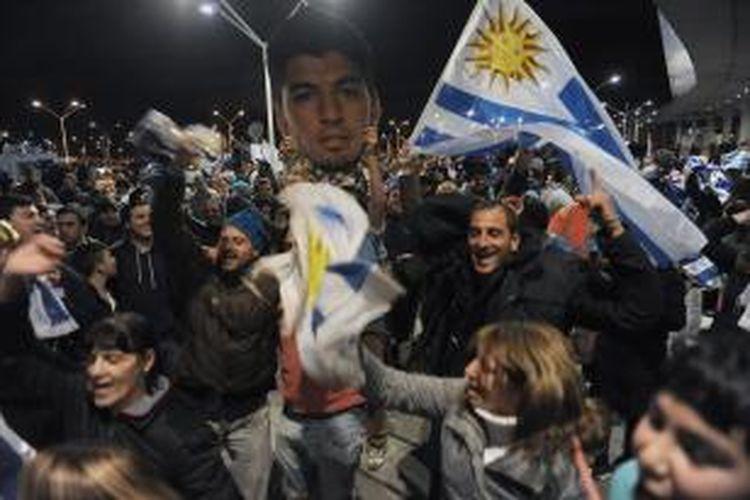 Publik Uruguay menunggu kedatangan pemain tim nasional mereka, Luis Suarez, di Bandara Internasional Carrasco, di Ciudad de la Costa, Canelones, pada Kamis (26/6/2014). Timnas Uruguay masih bermain di Piala Dunia 2014 Brasil, tetapi Suarez pulang lebih dulu karena agretisasinya dicabut FIFA, berkaitan dengan tindakannya menggigit bek Italia, Giorgio Chiellini, pada pertandingan Grup D Piala Dunia, di Estadio Das Dunas, Natal, Selasa (24/6/2014).