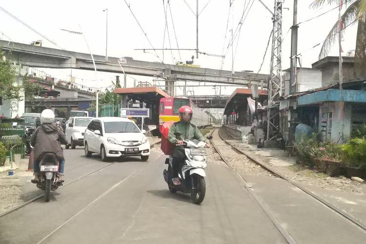 Para pengguna jalan melewati jalur perlintasan kereta tanpa palang di Stasiun Ancol.