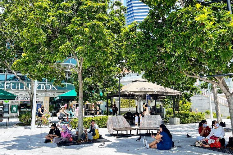 Asisten Rumah Tangga (ART) terlihat menggelar tikar berpiknik di Taman Merlion, Marina Bay dengan jumlah maksimum 2 orang pada hari pertama pemberlakuan lockdown parsial Singapura (16/5/2021)