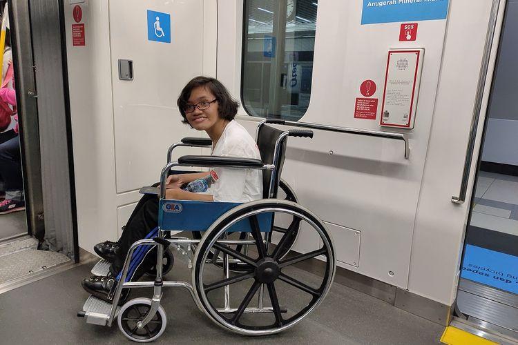 Maria (21), tengah mencoba fasilitas tempat khusus bagi penyandang disabilitas berkursi roda di dalam MRT, Selasa (3/12/2019).