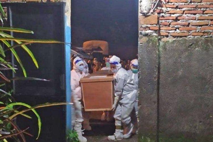 Petugas tengah melakukan proses pemakaman jenazah M (41) warga Desa Kajar, Tenggarang, Bondowoso secara protokol Covid-19. Anaknya sempat menolak pemakaman secara protokol Covid-19 sambil mengancam dengan senjata tajam mirip sebilah pedang.