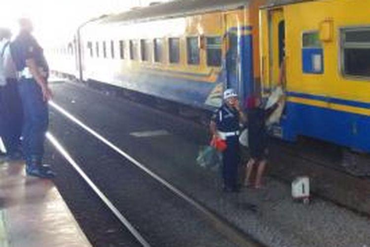 Petugas menertibkan salah satu penumpang kereta yang turun sembarangan ke rel perlintasan saat berhenti di stasiun Palmerah, Sabtu (16/5/2015) pagi.