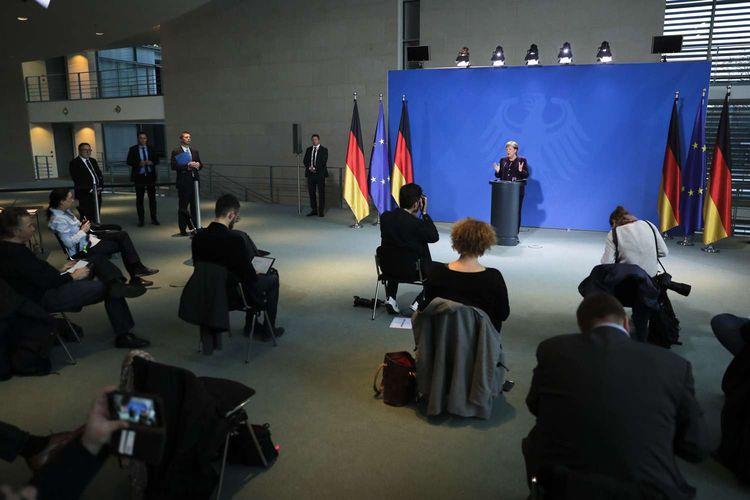 Kanselir Jerman Angela Merkel memberikan keterangan pers di depan sejumlah jurnalis yang duduk berjarak di  Berlin, Jerman, 16 Maret 2020. Menjaga jarak aman antar warga menjadi salah satu cara yang dianjurkan untuk mencegah penyebaran virus corona.