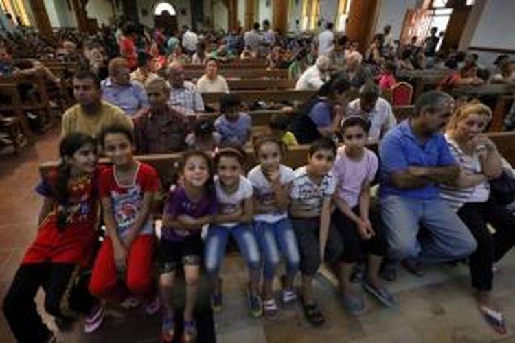 Warga Kristen Irak yang melarikan diri dari kekerasan di Desa Qaraqush, sekitar 30 kilometer Provinsi Nineveh, tiba di Gereja Saint-Joseph di Kota Arbil, wilayah otonomi Kurdistan Irak, 7 Agustus 2014. Mereka melarikan diri setelah ISIS merebut Qaraqush.