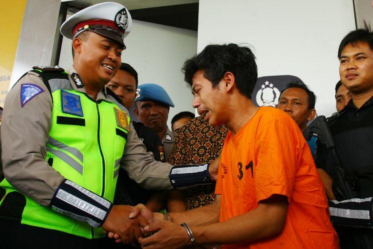 AS, pemuda yang merusak motornya sendiri saat kena tilang, menangis saat meminta maaf kepada Bripka Oky (kiri) Polantas yang dimaki-makinya saat menilang, di Mapolres Tangerang Selatan, Banten, Jumat (8/2/2019). Kepolisian Sektor Tangerang Selatan menetapkan AS (21) sebagai tersangka pengrusakan dan pemalsuan dokumen kendaraan bermotor. ANTARA FOTO/Muhammad Iqbal/ama.