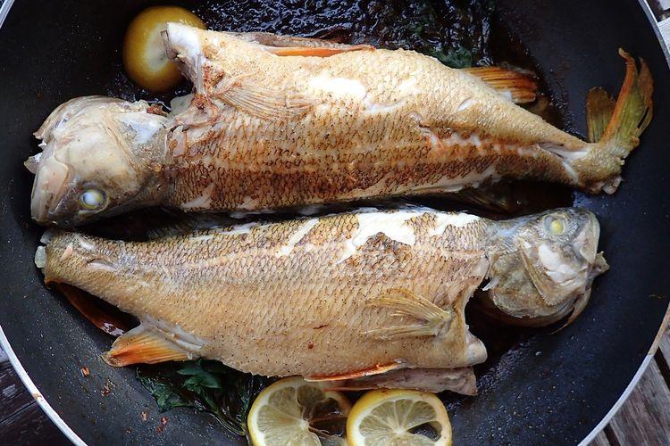 Ilustrasi ikan sedang digoreng dengan bumbu.