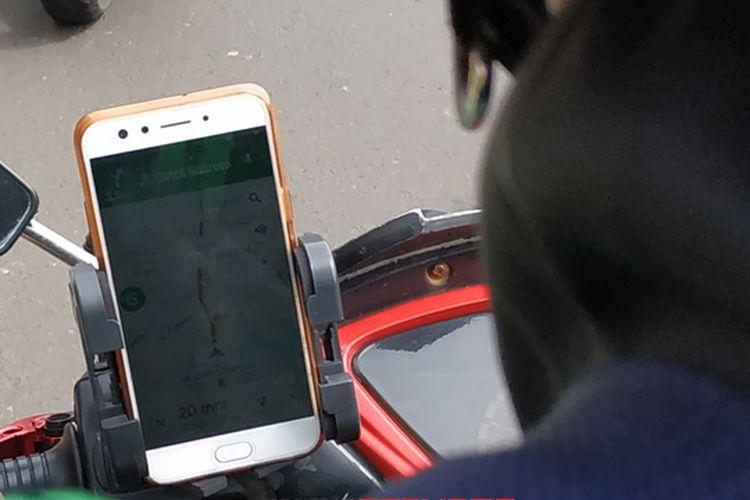 Ojek online menggunakna GPS pada ponsel saat berkendara mengantar dan menjemput penumpang.