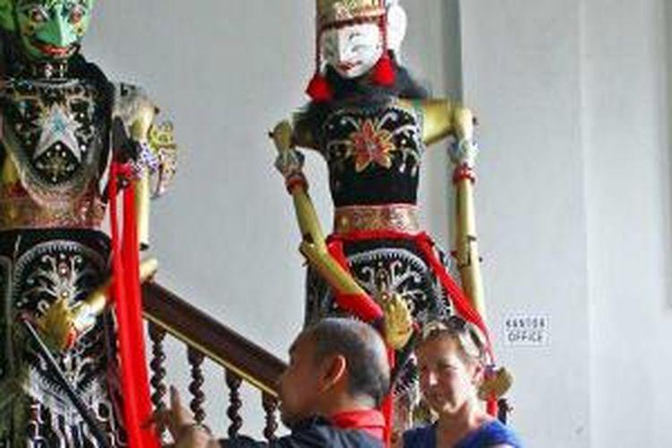 Seorang pemandu wisata sedang menjelaskan tentang Museum Wayang pada pengunjung yang merupakan wisatawan mancanegara.
