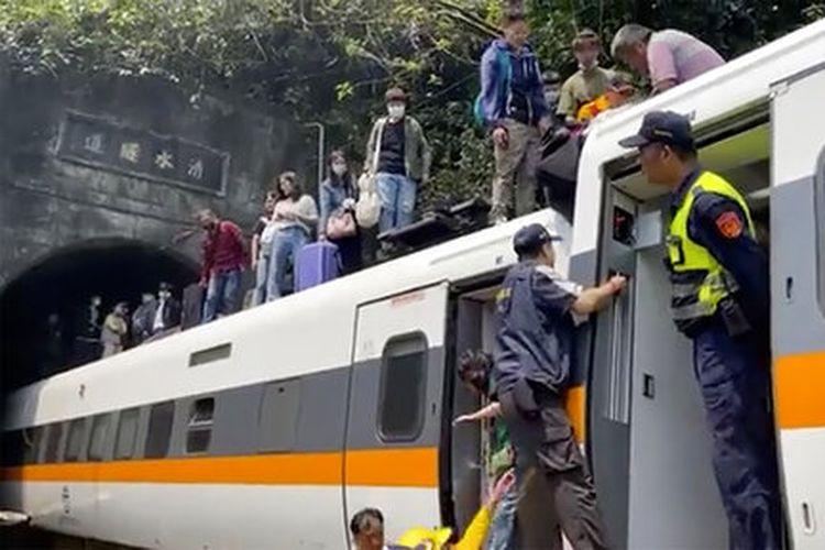 Para penumpang dibantu turun dari kereta api yang tergelincir di Hualien, Taiwan, pada Jumat (2/4/2021). Sebagian gerbong kereta api tersebut tergelincir di sepanjang jalur pantai timur Taiwan pada Jumat.