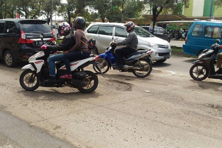 Kondisi Jalan Raya Jakarta-Bogor di Perempatan Gaplek, Tangsel yang penuh lubang. Semua kendaraan melambat untuk menghindari lubang-lubang berdiameter 20-30 cm dengan kedalaman 10-20 cm. Foto diambil Selasa (30/1/2018).