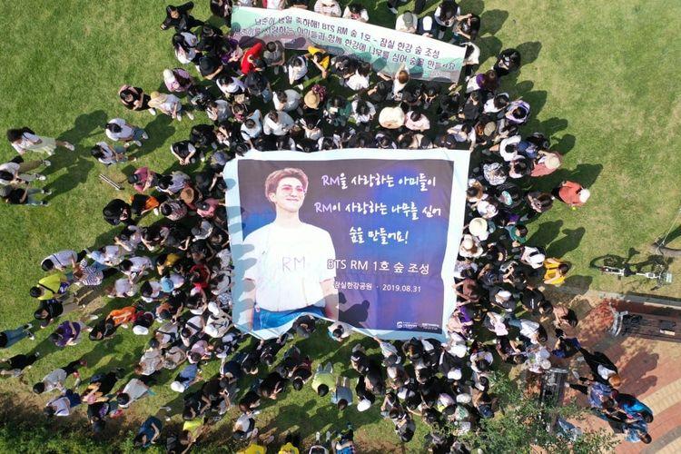 Para penggemar menggalang aksi tanam pohon untuk membangun hutan kota di kawasan Jamsil Hangang Park, Seoul, untuk menyambut ulang tahun ke-25 RM BTS.