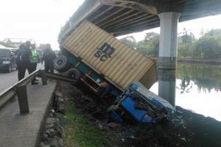 Sebuah truk kontainer terguling ke Kali Ancol, Jalan RE Martadinata, Ancol Pademangan, Jakarta Utara, Jumat (26/6/2015),