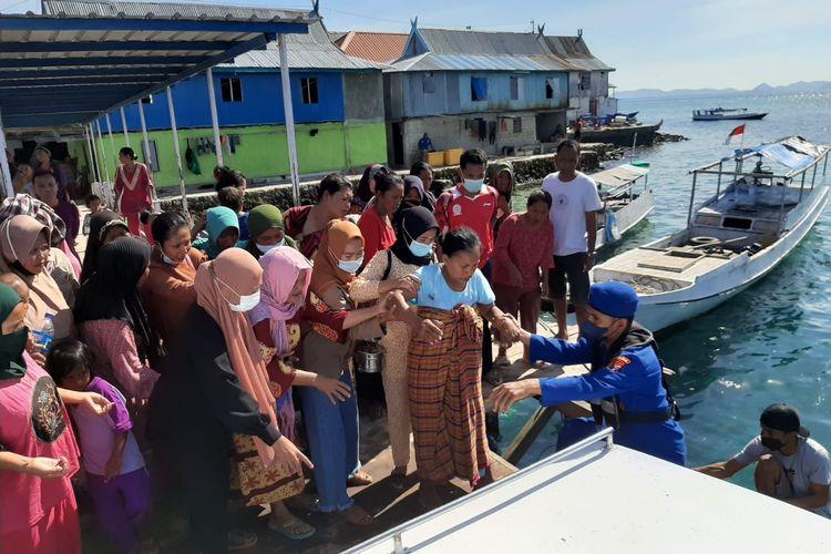 Anggota Direktorat Polairud Polda Nusa Tenggara Timur (NTT), membantu mengevakuasi seorang ibu hamil yang akan melahirkan dari  Pulau Mesah ke Pulau Flores, Labuan Bajo, Kabupaten Manggarai Barat, Nusa Tenggara Timur (NTT)