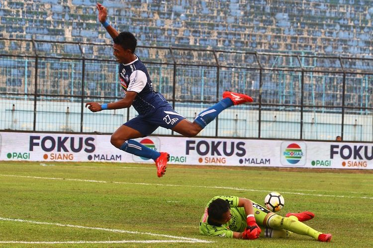 Pesepak bola Arema FC,  Dedik Setiawan (kiri) melompat untuk menghindari tubuh penjaga gawang Bali United, I Made Wardana (kanan) dalam pertandingan Liga 1 di Stadion Kanjuruhan, Malang, Jawa Timur, Sabtu (20/10/2018). Arema mengalahkan Bali United dengan skor akhir 3-1. ANTARA FOTO/Ari Bowo Sucipto/foc/18.