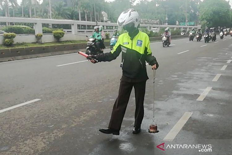 Relawan Sapu Bersih (Saber) Abdul Rohim melakukan penyapuan dengan magnet saat razia ranjau paku di Jalan Gatot Subroto, Jakarta Selatan