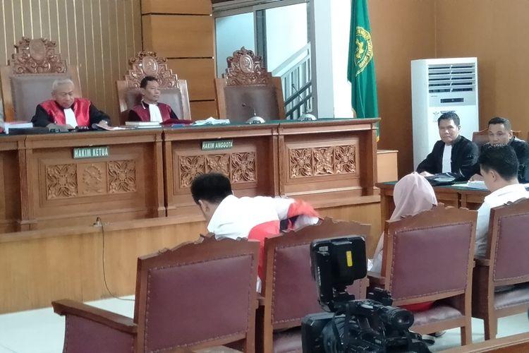 Pablo Benua dan Galih Ginanjar membuka rompi tahanan di ruang sidang Pengadilan Negeri Jakarta Selatan, Senin (9/12/2019)
