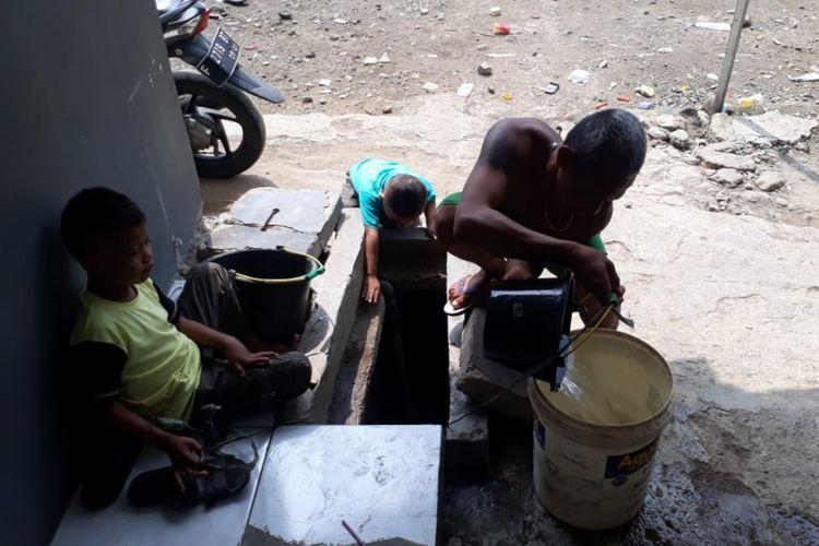 Seorang warga sedang menimba air sumur akibat kesulitan mendapat air bersih akibat sambungan pipa milik PDAM Kota Bogor mengalami kebocoran, Jumat (7/6/2019).