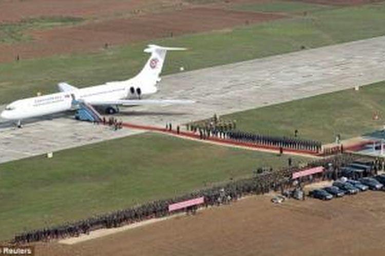 Dalam foto ini terlihat pesawat jet Ilyushin Il-62 yang digunakan sebagai pesawat kepresidenan Korea Utara tengah mendarat di sebuah lokasi yang tak disebutkan namanya, sementara karpet merah dan sepasukan tentara bersiap menyambut Kim Jong Un.