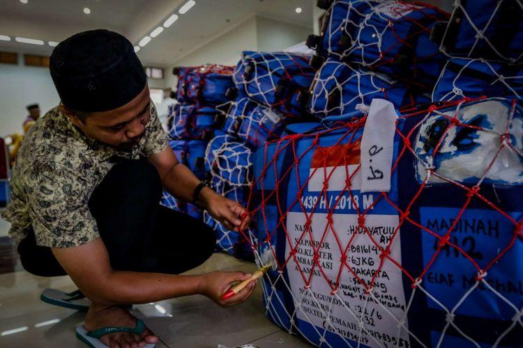 Petugas memberi tanda pada barang bawaan calon jemaah haji Kelompok Terbang (Kloter) 6 di Asrama Haji Pondok Gede, Jakarta, Rabu (18/7/2018). Sebanyak 24.524 calon jemaah haji dan 315 petugas akan diberangkatkan dari Asrama Haji embarkasi Jakarta.