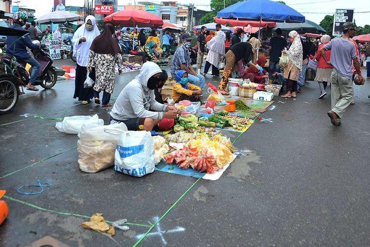 Suasana di lapak relokasi Pasar Tradisional Lemabang Palembang, Sumatera Selatan, Selasa (5/5/2020). Pasar Tradisional Lemabang yang mulai menerapkan jaga jarak dengan menyediakan lapak relokasi ini terkendala kurangnya lahan bagi pedagang dan padatnya pembeli.