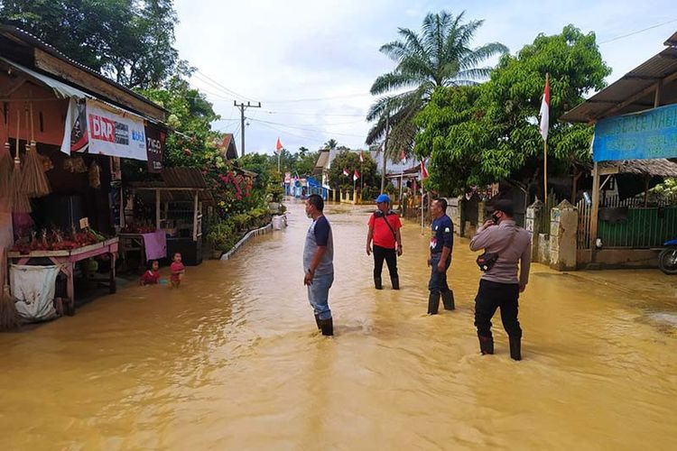 Warga melintas di genangan air di Indra Makmur Kabupaten Aceh Timur, Selasa (24/8/2021).