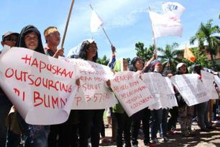 Sebagian buruh di Manado yang berdemo membawa poster yang bertuliskan tuntutan mereka.