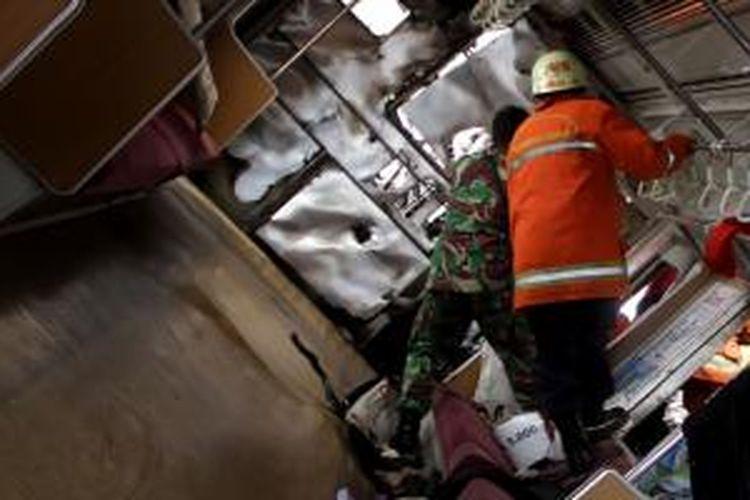Seorang anggota kepolisian memeriksa bagian dalam gerbong KRL Commuter Line jurusan serpong-Tanah Abang di Jalan Bintaro Permai, Jakarta Selatan, Senin (9/12/2013).