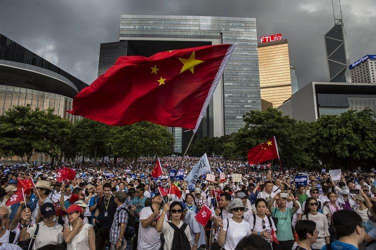 Puluhan ribu orang yang mengaku sebagai massa pro-pemerintah menggelar aksi mendukung aparat kepolisian Hong Kong di luar parlemen, Minggu (30/6/2019).