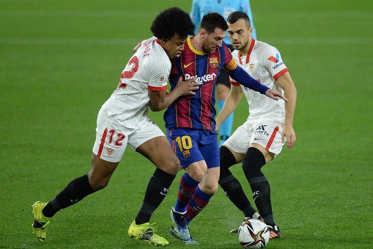 Megabintang Barcelona, Lionel Messi, berduel dengan bek Sevilla, Jules Kounde, pada leg pertama semifinal Copa del Rey yang berlangsung di Stadion Ramon Sanzhez Pizjuan, Kamis (11/2/2021) dini hari WIB.