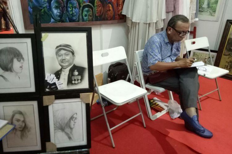 Pelukis sedang mengerjakan sketsa wajah di Bekasi Expo 2017