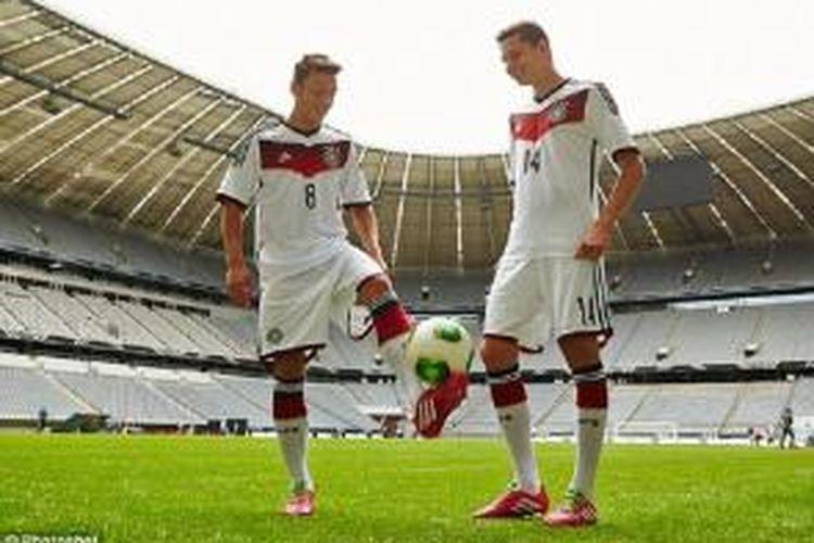 Mesut Oezil dan Julian Draxler saat peluncuran kostum baru tim nasional Jerman di Stadion Allianz, Munchen, Selasa (12/11/2013). Kostum tersebutakan digunakan dalam perhelatan Piala Dunia 2014 di Brazil.