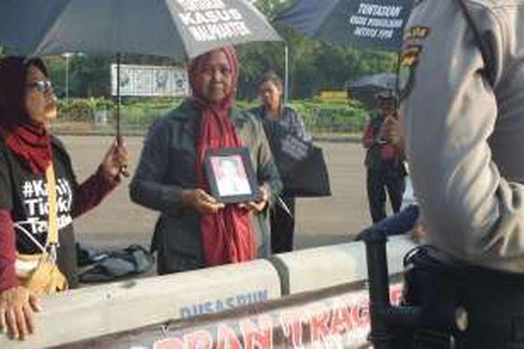 Maria Sanu, ibu korban kerusuhan Mei 1998, sedang berdiri sambil memegang foto anaknya yang menjadi korban kerusuhan, dalam Aksi Kamisan ke 443 di depan Istana Negara, Kamis (19/5/2016).