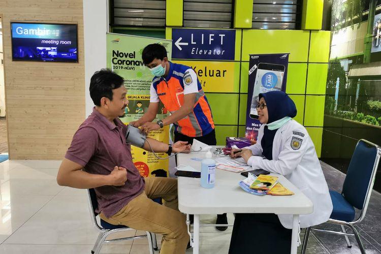 Penumpang sedang melakukan cek kesehatan di Stasiun Gambir.