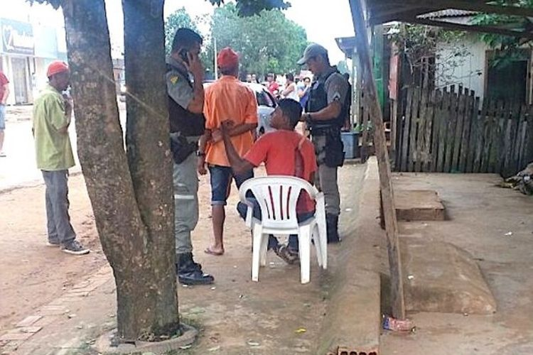 Elionardo Nascimento (kaus merah) duduk di kursi berbicara dengan seorang polisi sambil menunggu datangnya ambulans. Bisa dilihat sebilah pisau masih menancap di punggungnya.