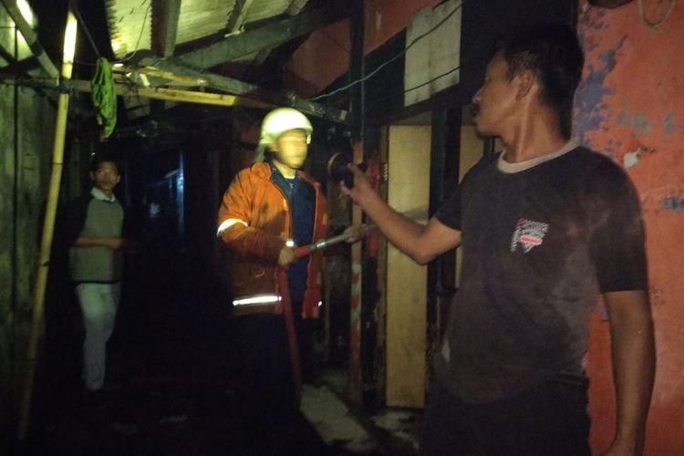 Petugas pemadam kebakaran dibantu warga tengah memadamkan api yang menghanguskan 12 kontrakan di Desa Pinayungan, Kecamatan Telukjambe Timur, Kabupaten Karawang, Jumat (7/9/2018).